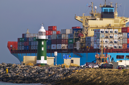 container ship passing a lighhouse at Fremantle ports, western australia, australia